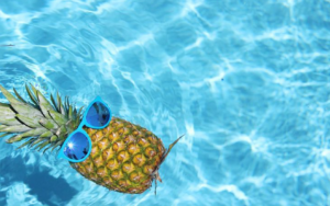 a pineapple with sunglasses on swimming in a pool for some unknown reason